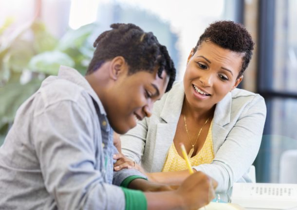 A loving mid adult mother sits at a table with her teenage son.  She grabs his arm as she praises the hard work he is doing on his homework.